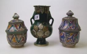 A pair of pottery lidded pots: with hand painted and metal decoration together with a similar twin