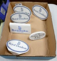 A collection of Royal Doulton Arthur Woods Ceramic Counter Top Advertising Name Plaques(6)