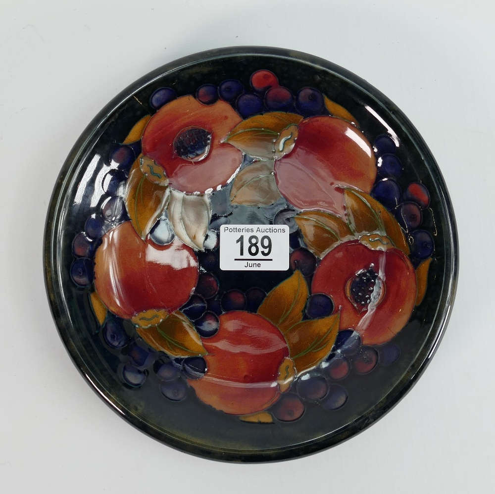 Moorcroft shallow dish in the pomegranate pattern: 22cm wide, hairline from edge to centre.