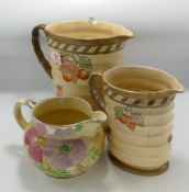 Crown Ducal Graduated Ribbed Jugs: together with Arthur Woods hand decorated similar item, height of