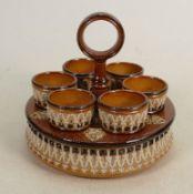 A Doulton Lambeth salt glazed egg stand and egg cups: 6 egg cups, diameter 17cm.