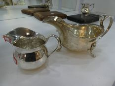 Two silver jugs, one being hallmarked London 1933, Pearce & Sons Ltd, Silversmiths, dented, together