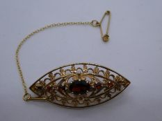 9ct Yellow gold oval brooch set with faceted garnets, marked 375 on pin, with safety chain, approx..