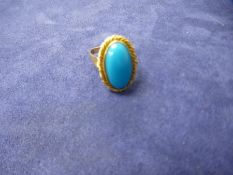Unmarked yellow gold dress ring with large oval turquoise stone, marks worn, gross weight 6.7g, size