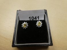 Pair of 18ct white and gold cluster earrings with central yellow sapphire surrounded by diamond chip