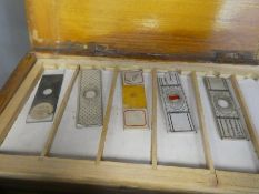 A quantity of early 20th century medical glass microscopic slides and a portable microscope