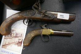 An old flintlock pistol and a small percussion pistol