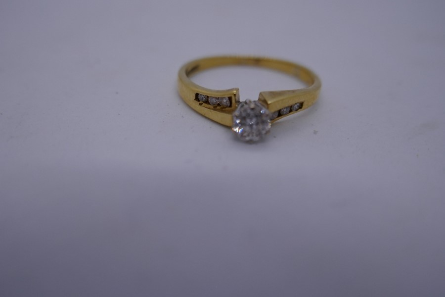 18ct yellow gold solitaire diamond ring, the shoulders set with diamonds, marked 750, size size O, 2