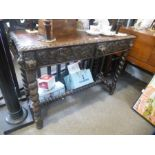 An old carved oak hall table having pierced back with two drawers on barley twist legs, 121cms