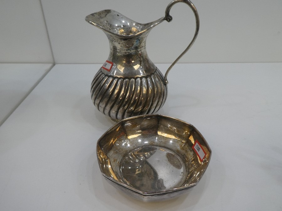 A silver jug with half reeded decoration, marked H and A 100, along with a silver Octagonol dish ma