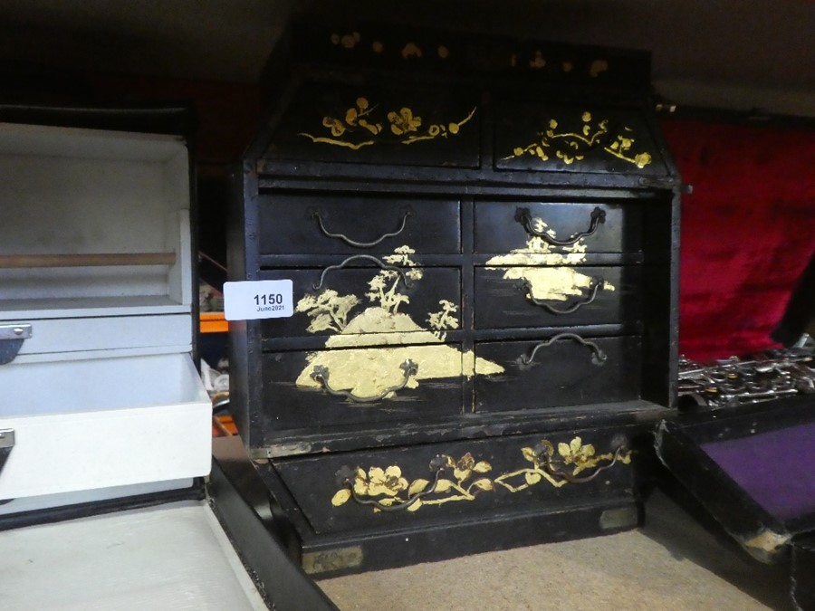 A small black case containing medicine bottles and a vintage wooden oriental storage case with 9 sma
