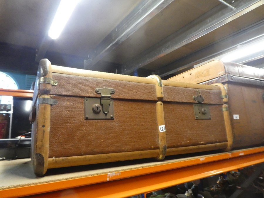 A metal trunk and another wooden metal bound trunk