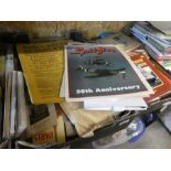 A shelf of mixed books and ephemera to include programmes, guide books, newspapers, nautical books,