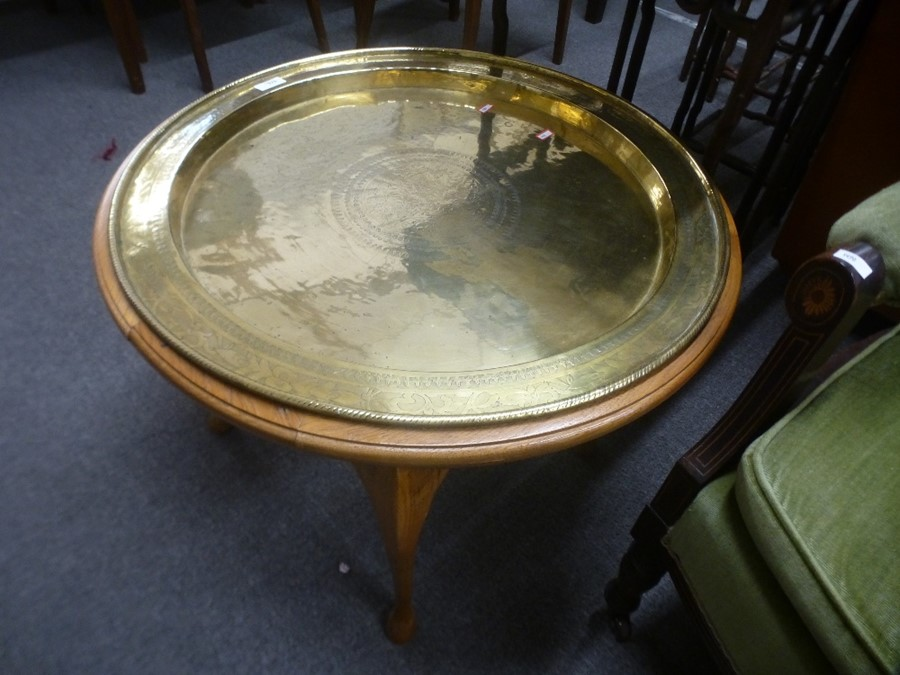 A circular brass tray top table on cabriole legs