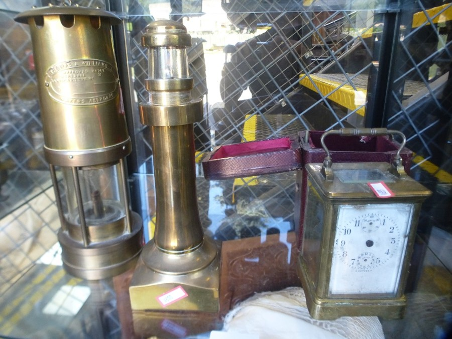 An old brass miners lamp, a carriage clock and a brass lighthouse lamp