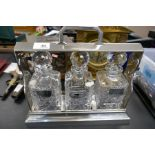 A silver plated tantalus having three glass decanters, two with silver wine labels