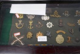 A small glazed display case containing military badges and similar.