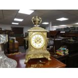 An early 20th century ornate brass chiming mantel clock with urn surmount and scroll feet