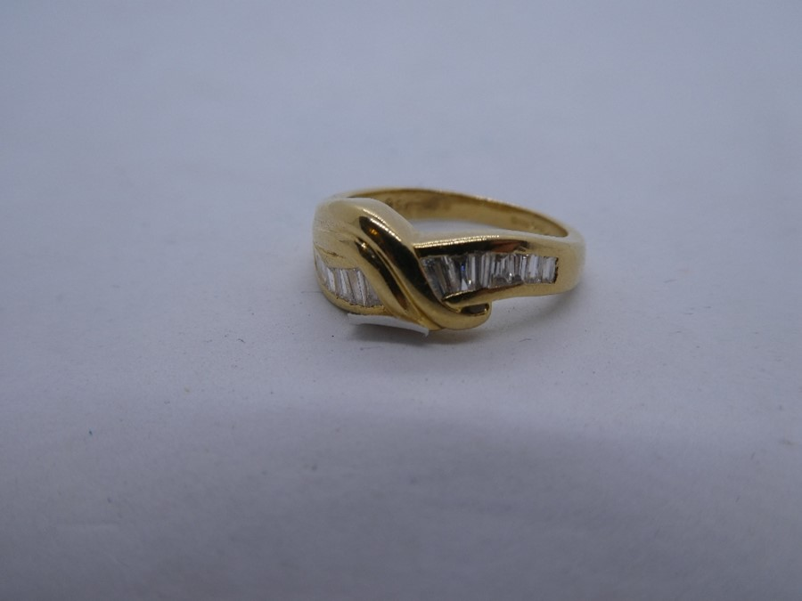 18ct yellow gold crossover design ring with tapered baguette cut diamond to shoulder, marked 750, ap