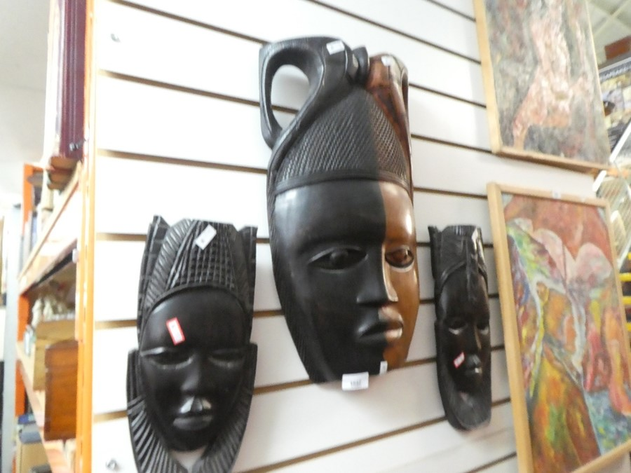 Three carved African masks one of large proportion and heavy