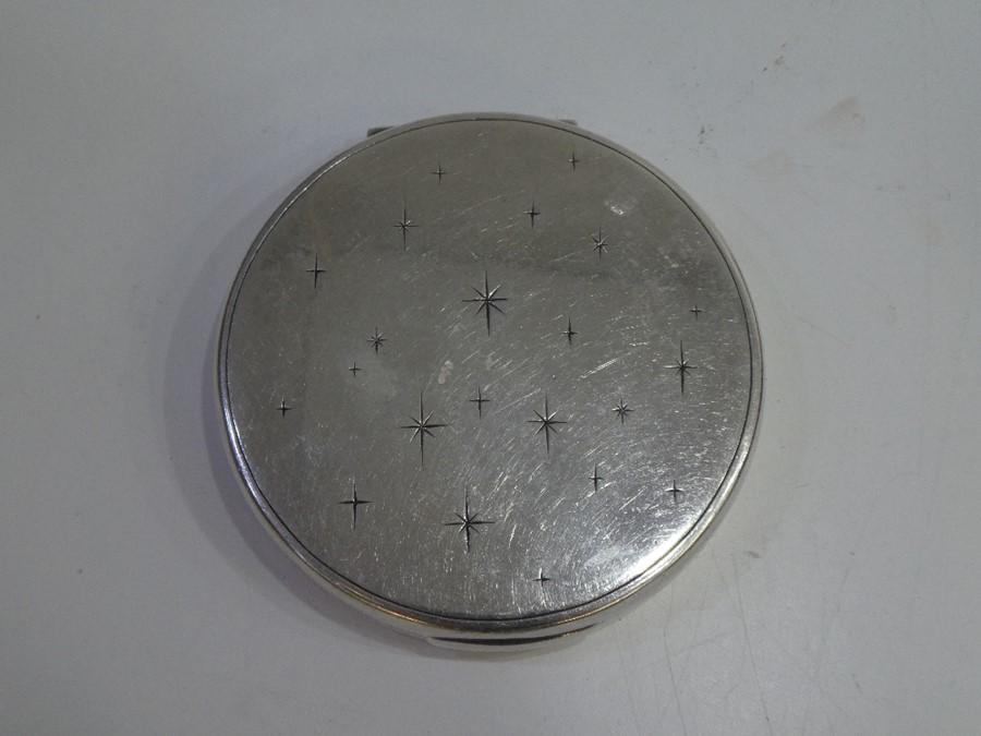 A decorative sterling silver compact mirror decorated with pretty stars. A decorative, ornate piece