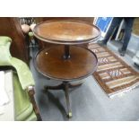 An antique mahogany two tier dumb waiter on a tripod base