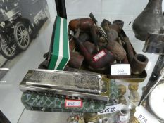 A selection of old pipes and two harmonicas, one named 'The Super Chromonica M Hohner'