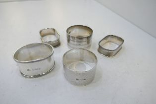 A selection of five silver napkin rings, one matching pair. With various hallmarks and designs inclu