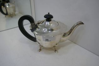 A silver smaller teapot with pretty scalloped edge lid and ebonised wood handle and knop. On four fe