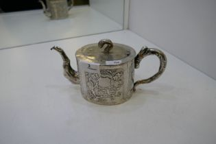 A Chinese teapot marked Kucheung with floreated design embossed on the body. Central vacant cafonche