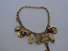9ct yellow gold charm bracelet hung with 10 charms to include 18 key, elephant, cello, ship, heart,