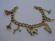 9ct yellow charm bracelet, hung with seven 9ct yellow gold charms including a gavel, stork, harp and