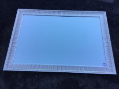 A large contemporary mirror, the bevelled plate in ribbed silvered frame. (35.25in x 51in)
