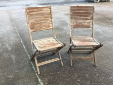 A pair of folding teak garden chairs with slatted backs & seats on rectangular legs. (2)