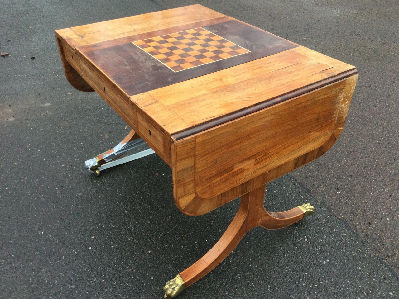 A walnut sofa games table, the rectangular rosewood crossbanded top with drop leaves having
