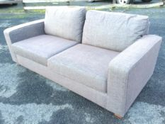 A contemporary upholstered Marks & Sparks sofa with loose cushions and rectangular platform arms,
