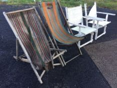 A pair of folding deck chairs, the striped canvas seats knackered; and a pair of folding hardwood