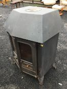A cast iron wood/solid fuel stove with angled glazed doors having fitted back boiler, raised on