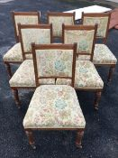 A set of six late Victorian oak dining chairs with floral brocade upholstery, the backs with moulded