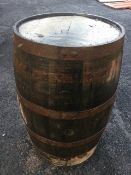 An old oak whiskey barrel, the staves bound by five metal strap bands. (35in)