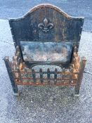 A cast iron dog grate with arched panelled back having applied fleur-de-lils motif, behind a