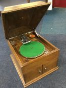 An oak cased His Masters Voice wind-up gramophone, with rectangular moulded top above a cabinet with