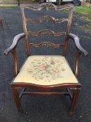 A mahogany ladderback elbow chair with four pierced anthemion carved rails, the shaped arms with