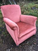 An upholstered armchair with padded back and arms above a sprung seat, raised on bun feet.