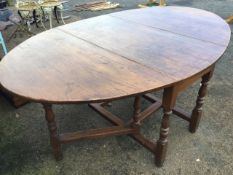 An oval oak dining table, the top with two drop leaves supported on baluster turned columns joined