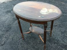 An oval mahogany occasional table, the moulded top on reeded column legs with applied floral