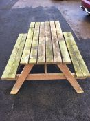 A garden picnic table and bench with slatted rectangular top above two seats on angled supports. (