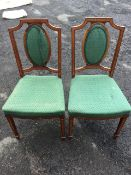 A pair of Edwardian mahogany satinwood banded chairs with oval upholstered panels to backs above