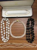 A cased double-strand pearl choker with 9ct gold bun shaped embossed clasp; a pair of silk black &