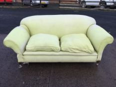 A drop-arm country house sofa with padded back and arms above loose cushions with sprung seat,